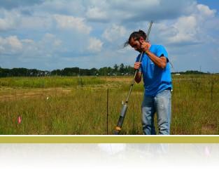 Taking deep soil core samples in E120.